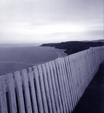 fence along clifftop overlooking ocean and islands