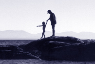 woman and child hopping from rock to rock in the ocean