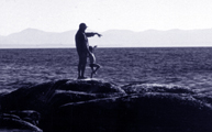 woman and child on rocks in ocean pointing to next rock