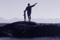 woman and child celebrate on rocks